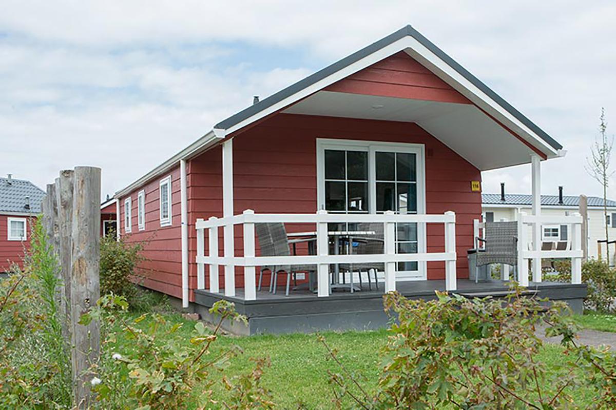 1. Lodge Mobilheim in klassischem rot mit Holzgeländer auf der Terrasse